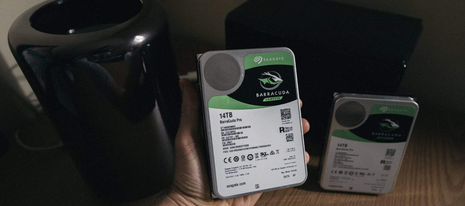 hand holding Seagate external hard drive in dark room