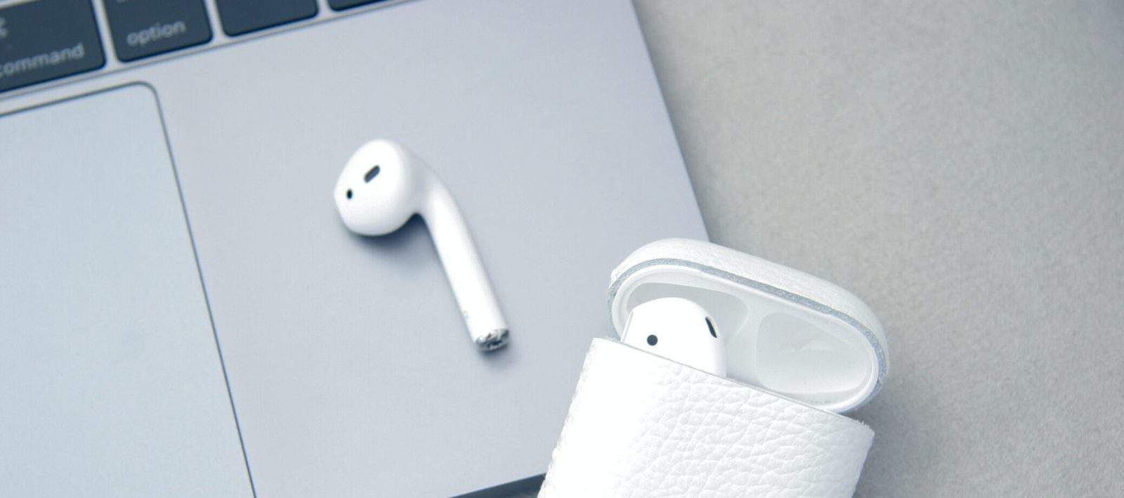 apple airpods on a table with macbook